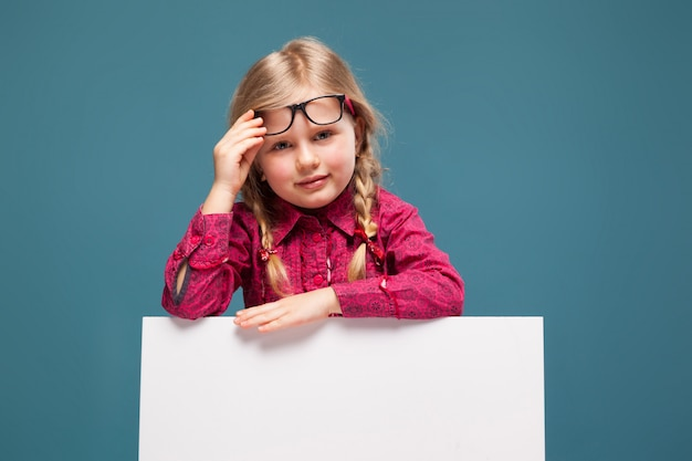 Очаровательная маленькая девочка в розовой рубашке, черных брюках и очках держит пустой плакат