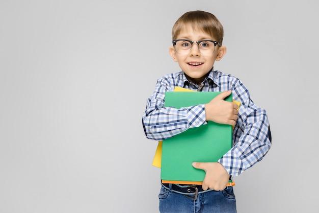 Очаровательный мальчик с вклетчатой рубашкой и светлыми джинсами стоит на сером фоне. мальчик держит в руках разноцветную папку с документами