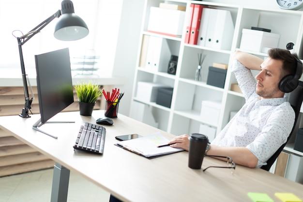 ヘッドフォンの若い男がコンピューターの机に座っています。