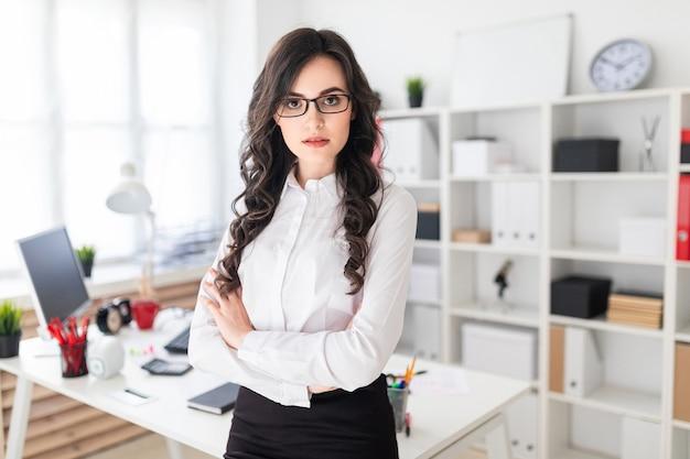 Красивая молодая девушка стоит возле офисного стола, сложив руки на груди.