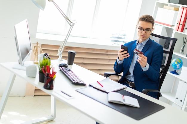 若い男がオフィスのテーブルに座って、銀行カードと電話を持っています。
