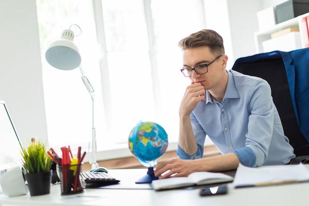 若い男がオフィスのコンピューターデスクに座って、地球を見て考えています。