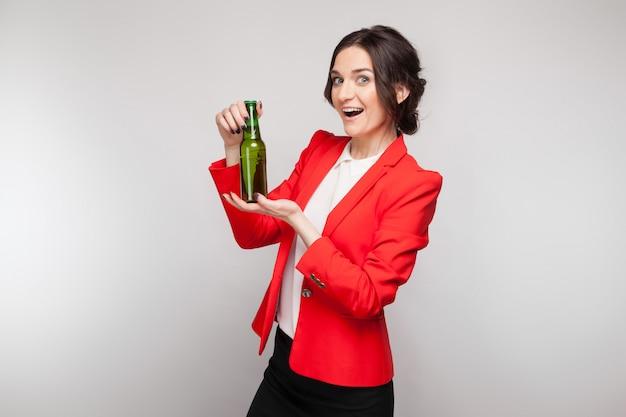 Картина привлекательная женщина в красном платье с зеленым пивом в руках