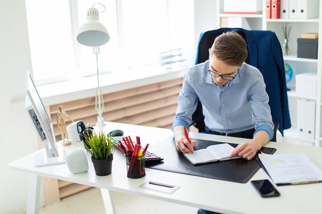 若い男がオフィスのコンピューターデスクに座って、ノートに書き込みます。