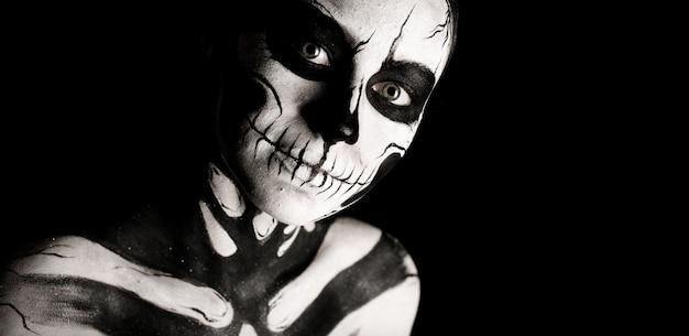 Изолированные на черном, широкоэкранный, крупным планом изображение, красивая молодая брюнетка кавказская женщина с черепом боди-арт, серые глаза, серьезный, томный взгляд