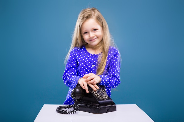 紫色のドレスのかわいい女の子は携帯電話を保持します