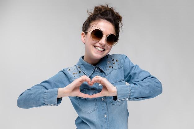 Молодая брюнетка девушка в черных очках. кошачьи очки. волосы собраны в пучок. девушка показывает руки сердца.