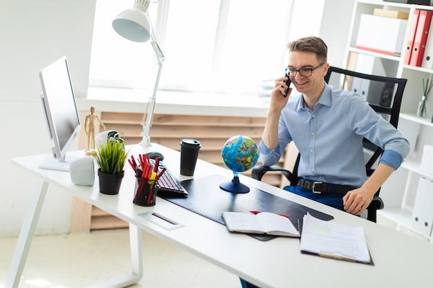 若い男がオフィスのコンピューターデスクに座って、電話で話していると、地球を見ています。