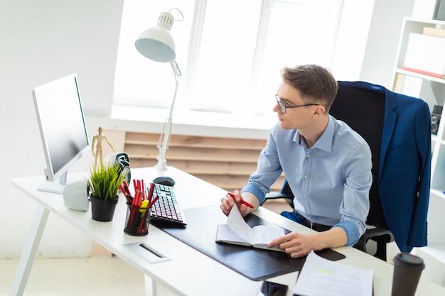 若い男がオフィスのコンピューターデスクに座って、ペンを手に持ってモニターを見ます。