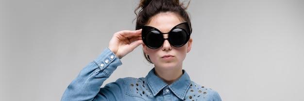 Молодая брюнетка девушка в черных очках. кошачьи очки. волосы собраны в пучок. девушка поправляет рубашку и очки.