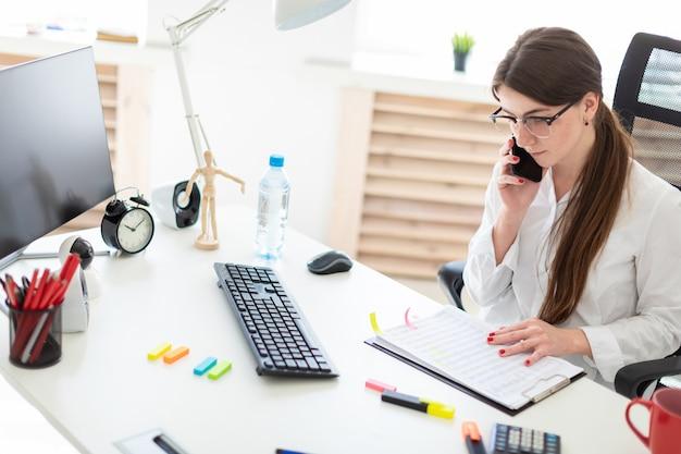 オフィスの机に座って、電話で話していると、ドキュメントでの作業の若い女の子