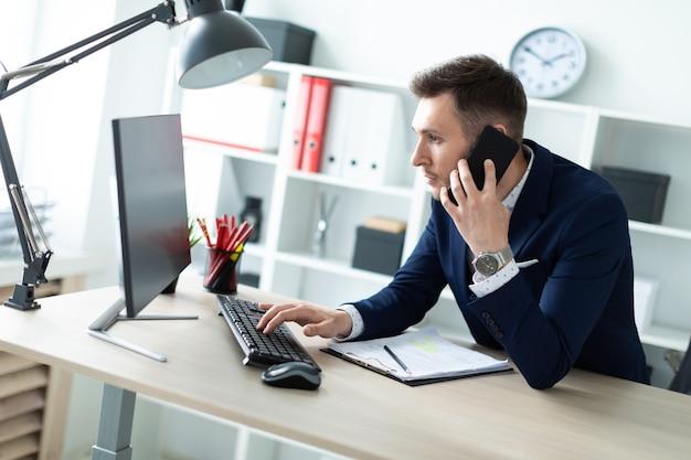 Молодой человек стоит возле стола в офисе, разговаривает по телефону и набирает текст на клавиатуре.