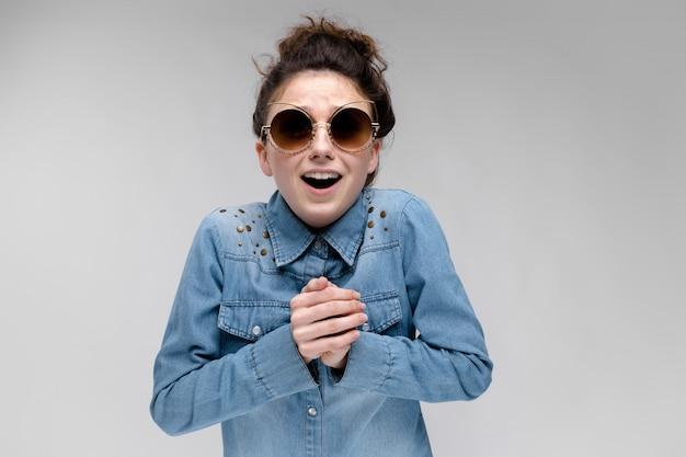 Молодая брюнетка девушка в черных очках. кошачьи очки. волосы собраны в пучок. девушка сложила руки на груди.