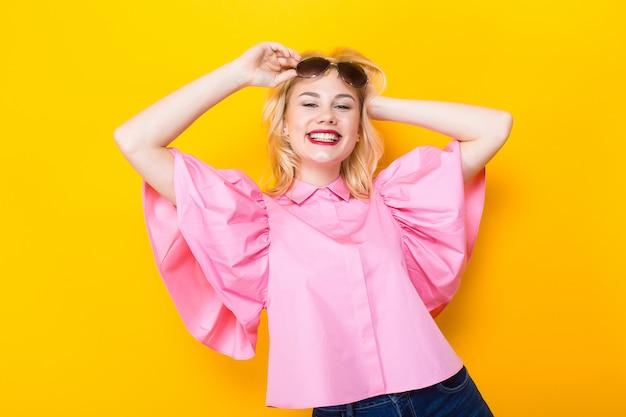 サングラスとピンクのブラウスで幸せな金髪女