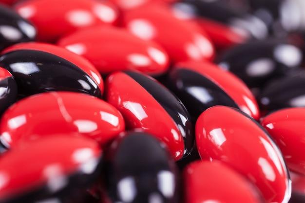 ミラーの背景に赤黒茶色の錠剤の散乱