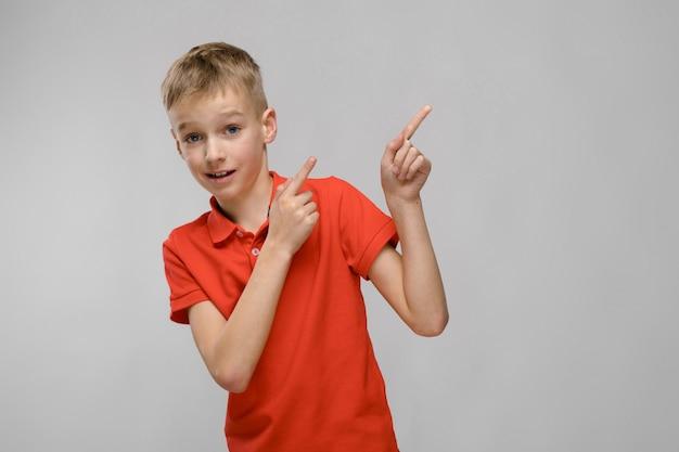 Портрет белокурого кавказского серьезного маленького мальчика в оранжевой футболке показывая на пустой области на серой предпосылке
