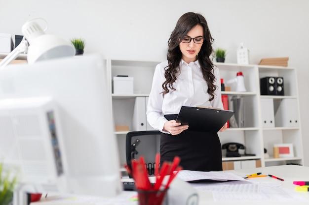 美しい若い女の子が事務机のそばに立ち、メモ用紙を持っています。