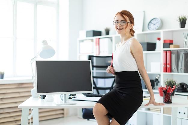Красивая молодая девушка в офисе села на стол и держала в руке красный карандаш. рядом с девушкой стоит монитор.
