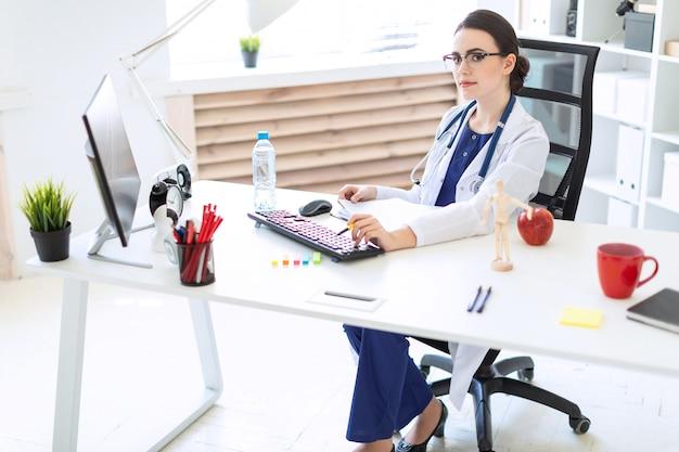 Красивая молодая девушка в белом халате сидит за компьютерным столом с документами и ручкой в руках.