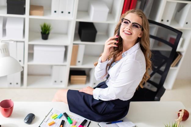 美しい少女がオフィスのテーブルに座って電話で話していました。女の子の前に書類があります。