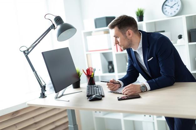 若い男がオフィスのテーブルの近くに立って、手に鉛筆を持ち、ドキュメントとコンピューターを操作します。