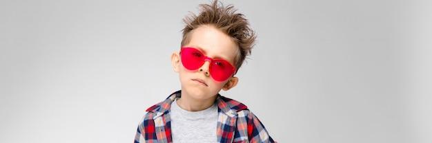 格子縞のシャツ、灰色のシャツ、ジーンズでハンサムな男の子は灰色の背景に立っています。赤いサングラスの少年