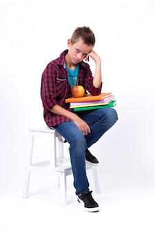 Уставший школьник европейской внешности в рубашке и джинсах сидит