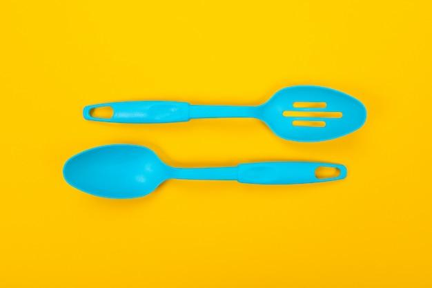 黄色の背景に分離されたプラスチックキッチンツール