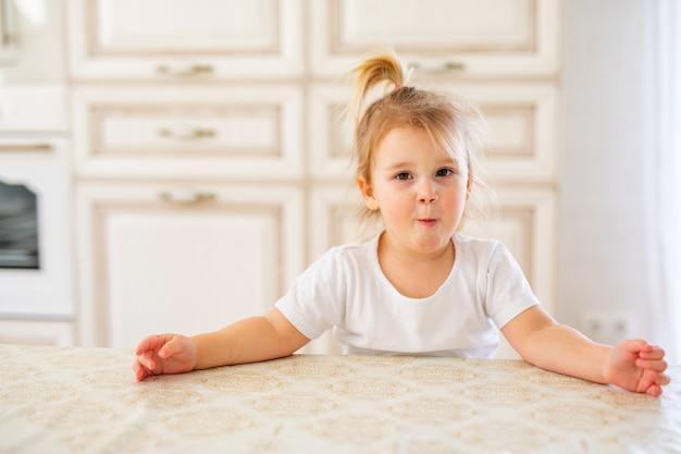 キッチンで朝食を持っている美しい金髪の赤ちゃん女の子。変な顔