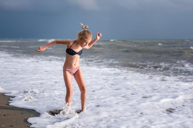 海の波でジャンプの女の子。水しぶきを伴うジャンプ。夏の晴れた日、海の海岸