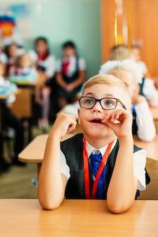 教室に座って、勉強、笑みを浮かべて大きな黒い眼鏡の金髪の少年。小学校での教育、学校初日