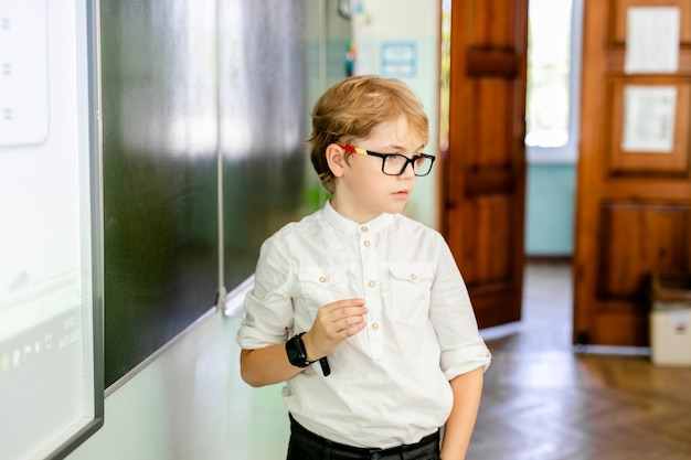 大きな黒いメガネとスマート思考の顔を作るチョークで学校の黒板の近くに立っている白いシャツを持った少年