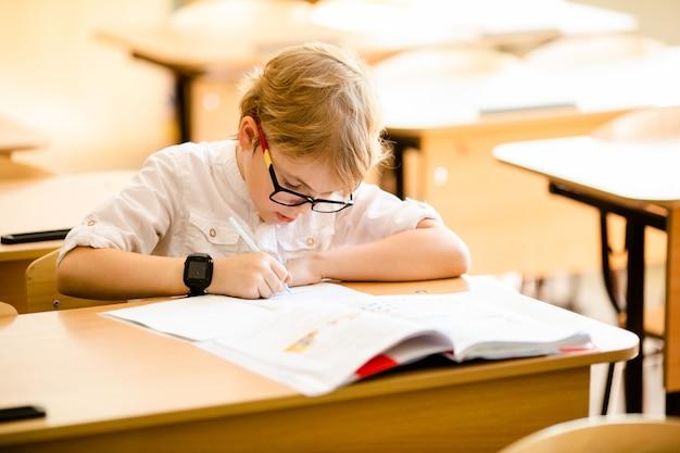 Счастливый милый умный мальчик сидит за столом в очках с поднятием руки.