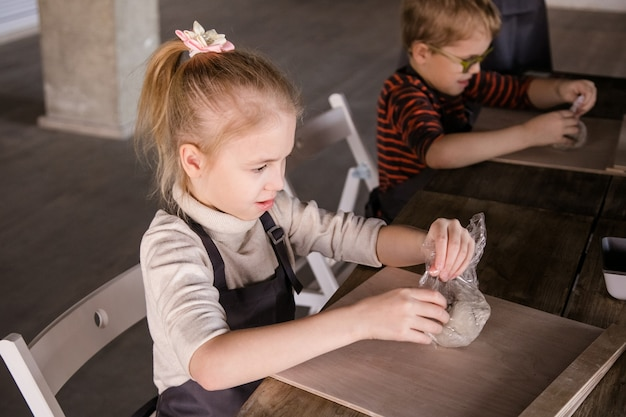 粘土からのブロンドの女の子の彫刻