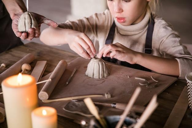 ブロンドの女の子は興味を持って粘土から彫刻します