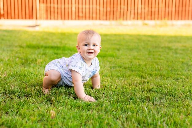フィールドの芝生の上の屋外幸せな面白い男の子の夏の肖像画。クロールを学ぶ子供
