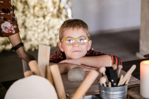 大きなメガネで小さな男の子が興味を持って粘土から彫刻します。