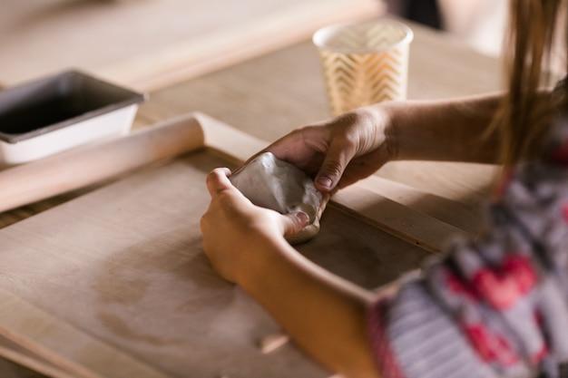 小さな男の子は興味を持って粘土から彫刻します。