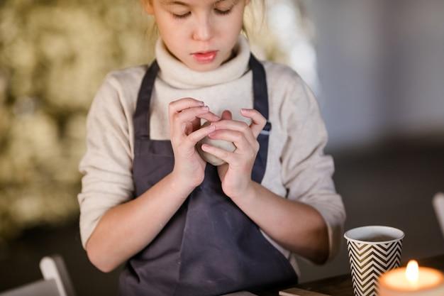 ブロンドの女の子は、スタジオで粘土から彫刻します。アートクラス