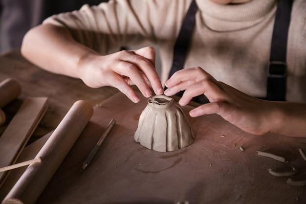 子供は粘土から彫刻します。手のクローズアップ