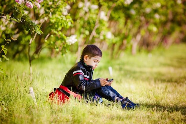 春の公園の芝生の上に座っている小さな男の子