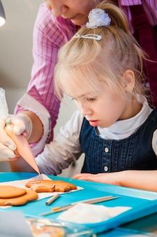 娘と彼女の母親が砂糖のアイシングでジンジャーブレッドを飾る