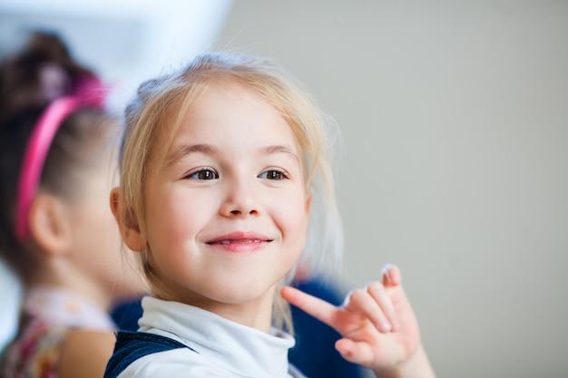 砂糖のアイシングでジンジャーブレッドを飾る幸せの小さなブロンドの女の子