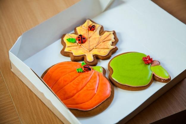 ハロウィーンのカボチャの形をした自家製ジンジャーブレッドクッキー。古い木製の背景に秋のカエデの葉