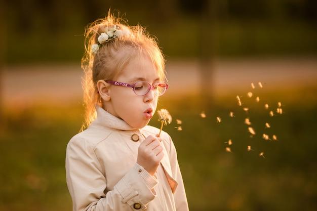 メガネと日没の秋の公園のタンポポで吹く光のコートで巻き毛の女子高生