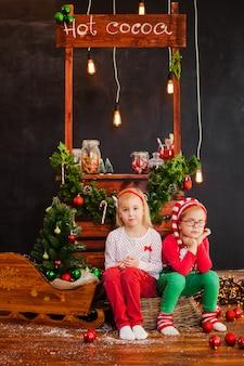 Улыбающаяся симпатичная белокурая девочка и мальчик сидят на деревянном полу с елочными шарами