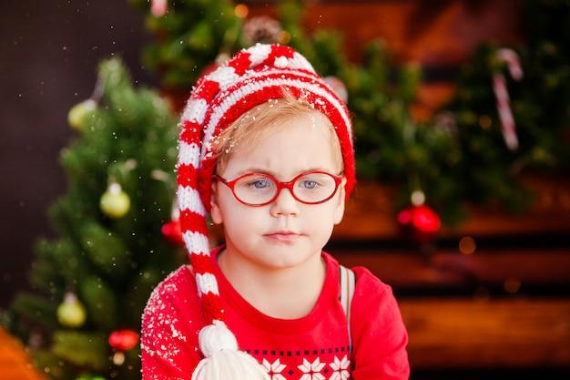 ブロンドの髪、青い目、サンタさんの帽子とメガネとかわいい男の子
