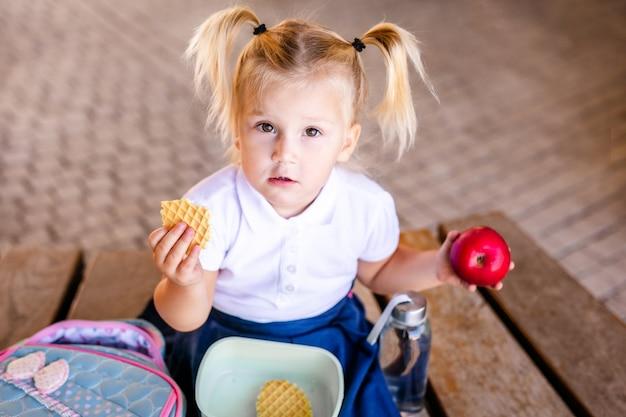 Милая очаровательны кавказских малышей девочка сидит и ест