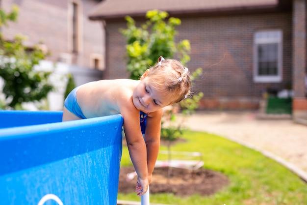 自宅の屋外スイミングプールに飛び込む赤い水着の幸せな女の子。泳ぐことを学ぶ女の赤ちゃん。子供のための水遊び。