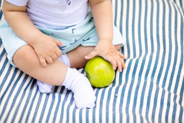 黄色の洋ナシを保持している小さな赤ちゃんの指